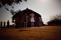Children playing outside under the full moon at night in Madi Opei, Uganda