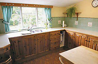 BNPS.co.uk (01202 558833)<br /> Pic: Mullucks/BNPS<br /> <br /> kitchen before.<br /> <br /> A retired couple dubbed 'the accidental upsizers' have put their luxury home on the market for a whopping £750,000.<br /> <br /> Jean and Desmond Lawton bought a suburban bungalow three years ago as they looked to downsize from a large property.<br /> <br /> But they soon decided that they didn't like the dated decour of the humble home and transformed it beyond recognition.<br /> <br /> They knocked down every internal retaining wall bar one to create an open-plan space and built a single-storey extension to the rear.