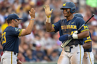 Michigan Wolverines designated hitter Jordan Nwogu (42) is greeted by head coach Erik Bakich (23) after scoring against the Florida State Seminoles during the NCAA College World Series on June 17, 2019 at TD Ameritrade Park in Omaha, Nebraska. Michigan defeated Florida State 2-0. (Andrew Woolley/Four Seam Images)