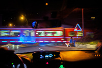 Switzerland. Canton Ticino. Agno. View at nighttime through a car 's windshield. Passing train at level crossing. The Lugano–Ponte Tresa Railway or Ferrovia Lugano–Ponte Tresa (FLP) is a local railway line. The line is 12.3 kilometres long and is operated by the Ferrovie Luganesi company. A woman holds a dog on leash. Agno is 5 km distant from Lugano.13.01.2018 © 2018 Didier Ruef