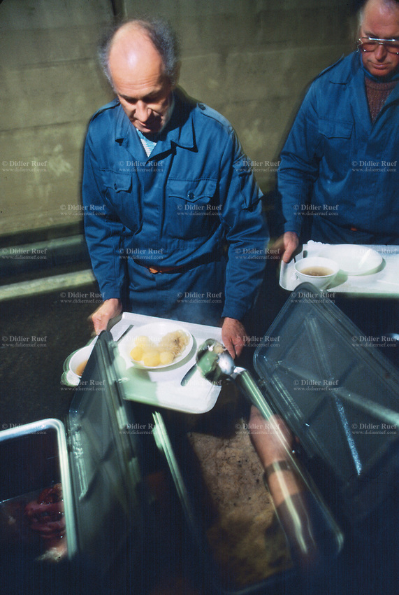 Switzerland. Canton Lucerne. Lunch time in the Sonnenberg tunnel in Lucerne during the largest civil defense exercise ever held in the country. Two men carry trays and receive food on plastic plates. A bowl of soup, a sausage, potatoes and sauerkraut. Sauerkraut is finely cut raw cabbage that has been fermented by various lactic acid bacteria.From 16 to 21 November 1987, almost 1200 men and women converted a motorway tunnel into perhaps the world's largest bunker structure. The civil protectors had to prove during the exercise «Ameise» ( Ants in english) that in an emergency more than 20,000 inhabitants of the city of Lucerne could survive here in the mountain for two weeks. The Sonnenberg Tunnel is a 1,550m  long motorway tunnel, constructed between 1971 and 1976. At its completion it was also the world's largest civilian nuclear fallout shelter, designed to protect 20,000 civilians in the eventuality of war or disaster. Based on a federal law from 1963, Switzerland aims to provide nuclear fallout shelters for the entire population of the country. The construction of a new tunnel near an urban centre was seen as an opportunity to provide shelter space for a large number of people at the same time. The giant bunker was built between 1970 and 1976 at a cost of 40 million Swiss francs. The shelter consisted of the two motorway tunnels (one per direction of travel), each capable of holding 10,000 people in 64 person subdivisions. A seven story cavern between the tunnels contained shelter infrastructure including a command post, an emergency hospital, a radio studio, a telephone centre, prison cells and ventilation machines. The shelter was designed to withstand the blast from a 1 megaton nuclear explosion 1 kilometer away. The blast doors at the tunnel portals are 1.5 meters thick and weigh 350 tons. The logistical problems of maintaining a population of 20,000 in close confines were not thoroughly explored, and testing the installation was difficult because it r