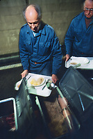 Switzerland. Canton Lucerne. Lunch time in the Sonnenberg tunnel in Lucerne during the largest civil defense exercise ever held in the country. Two men carry trays and receive food on plastic plates. A bowl of soup, a sausage, potatoes and sauerkraut. Sauerkraut is finely cut raw cabbage that has been fermented by various lactic acid bacteria.From 16 to 21 November 1987, almost 1200 men and women converted a motorway tunnel into perhaps the world's largest bunker structure. The civil protectors had to prove during the exercise «Ameise » ( Ants in english) that in an emergency more than 20,000 inhabitants of the city of Lucerne could survive here in the mountain for two weeks. The Sonnenberg Tunnel is a 1,550 m  long motorway tunnel, constructed between 1971 and 1976. At its completion it was also the world's largest civilian nuclear fallout shelter, designed to protect 20,000 civilians in the eventuality of war or disaster. Based on a federal law from 1963, Switzerland aims to provide nuclear fallout shelters for the entire population of the country. The construction of a new tunnel near an urban centre was seen as an opportunity to provide shelter space for a large number of people at the same time. The giant bunker was built between 1970 and 1976 at a cost of 40 million Swiss francs. The shelter consisted of the two motorway tunnels (one per direction of travel), each capable of holding 10,000 people in 64 person subdivisions. A seven story cavern between the tunnels contained shelter infrastructure including a command post, an emergency hospital, a radio studio, a telephone centre, prison cells and ventilation machines. The shelter was designed to withstand the blast from a 1 megaton nuclear explosion 1 kilometer away. The blast doors at the tunnel portals are 1.5 meters thick and weigh 350 tons. The logistical problems of maintaining a population of 20,000 in close confines were not thoroughly explored, and testing the installation was difficult because it r