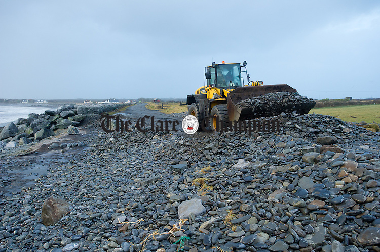A loader works on clearing the road between Rahona and Kilbaha where the sea delivered huge amounts of rocks and debris. Photograph by John Kelly.