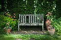 Old garden seat in front of yew hedge, flanked by Geraniums and Euphorbia, Vann House and Garden, Surrey, mid June.