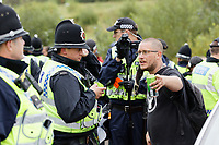 Pictured: The organiser is spoken to py police officers. Monday 31 August 2020<br /> Re: Around 70 South Wales Police officers executed a dispersal order at the site of an illegal rave party, where they confiscated sound gear used by the organisers in woods near the village of Banwen, in south Wales, UK.