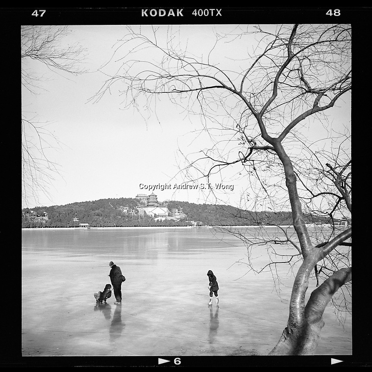 A Chinese girl skates as a man pushes his son on a frozen Kunming Lake against a backdrop of the Longevity Hill at the Summer Palace in Beijing, China January 2014. (Mamiya 6, 75mm, Kodak TRI-X film)
