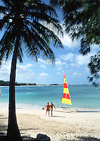 Perfect beach scene: couple walking on beach, with sailboat in background