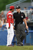 Batavia Muckdogs manager Angel Espada (4) argues a call with umpire Chris Scott during a game against the Staten Island Yankees on August 8, 2014 at Dwyer Stadium in Batavia, New York.  Staten Island defeated Batavia 4-2.  (Mike Janes/Four Seam Images)