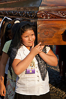 Antigua, Guatemala.  Semana Santa (Holy Week).  Young Girl Carrying an Anda (Float) of the Virgin Mary in a Religious Procession.