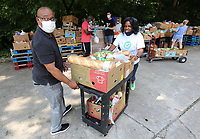 Pastor Curtiss Smith (left) and Monique Jones, director of Outreach and Evangelism at Saint James Missionary Baptist Church, move a cart full of food Tuesday, July 20, 2021, to the distribution area for the St. James Missionary Baptist Church Food Pantry at the Squire Jahagen Arts and Outreach Center located at 115 S. Willow Avenue in Fayetteville. St. James Missionary Baptist Church, Central EMS and the Arkansas Department of Health hosted a drive-up covid-19 vaccination clinic at the center during the food pantry distribution hours. Check out nwaonline.com/210721Daily/ and nwadg.com/photos for a photo gallery.(NWA Democrat-Gazette/David Gottschalk)