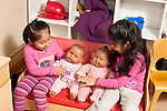 Education Preschool 3-4 year olds two girls playing imaginary game with dolls on small sofa between them