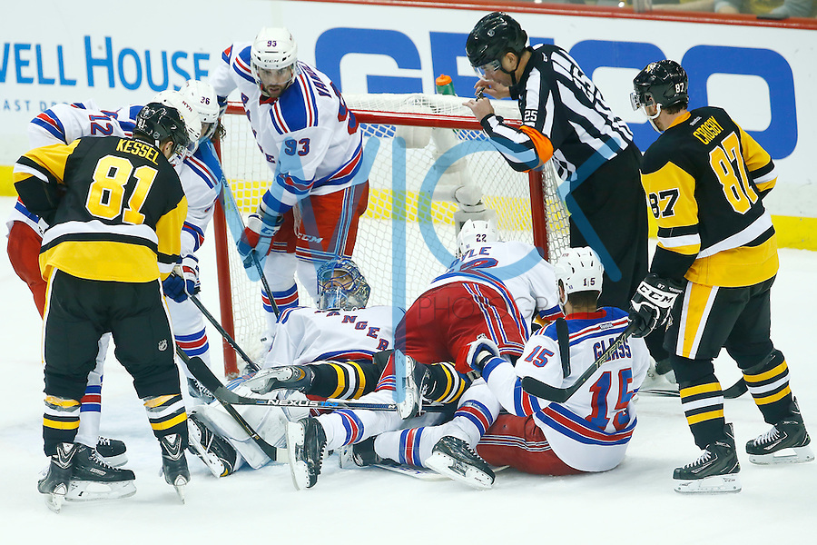 Henrik Lundqvist #30 of the New York Rangers makes a save in front of Phil Kessel #81 and Sidney Crosby #87 of the Pittsburgh Penguins in the third period during game two of the first round of the Stanley Cup Playoffs at Consol Energy Center in Pittsburgh, Pennsylvania on April 16, 2016. (Photo by Jared Wickerham / DKPS)