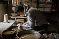 Japan, Mie Prefecture, Iga City. Family run Iga pottery studio, at least eight generations. Iga pottery is a special style using local hard clay with a high resistance to fire. The daughter is at least eighth generation and learned from her father, working at the potter's wheel. She's the youngest of four girls, but only two of them do pottery. It's a male oriented profession as the kneading is very physical. She stayed at a Zen monsatery for a year, and studied spiritual training as well as cooking school to apply these skills to her earthenware pottery. She finds making pottery very meditative and likes to imagine the food cooking in her pot as she's making it. Model released