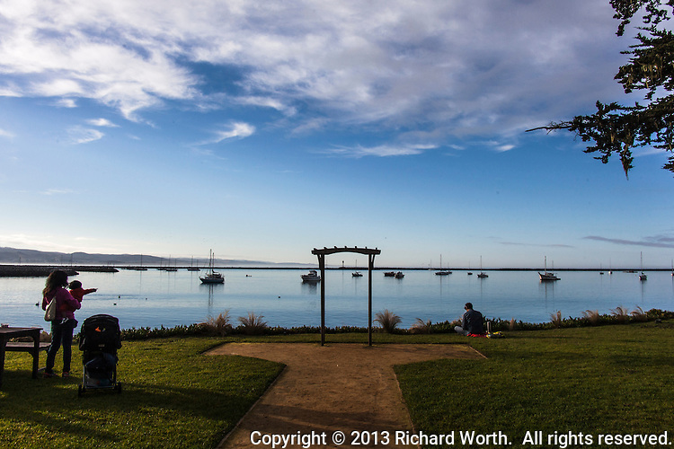 A mother and child share a morning view of Pillar Point Harbor with boats and sky and peace and quiet.