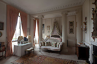 The bedroom is divided into a bed alcove and sitting and dressing area by classical columns