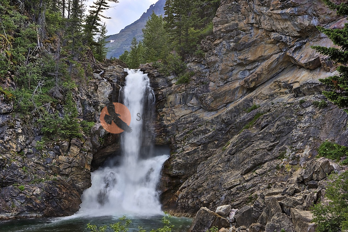 Running Eagle Falls also known as Trick falls in Glacier National Park with both falls rushing