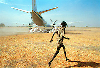 ©Sven Torfinn/Panos Pictures..South Sudan, 2001.Upper Nile region, village of Boeth, relief food brought by 'Save Harbor International Relief' planes are taking off, boy is running away from the dust and noise