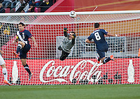 Slovenia's  Samir Handanovic punches out a cross over the USA's Carlos Bocanegra (left) and Clint Dempsey in the first half of the 2010 World Cup match between USA and Slovenia at Ellis Park Stadium in Johannesburg, South Africa on Friday, June 18, 2010.  The USA tied Slovenia 2-2.