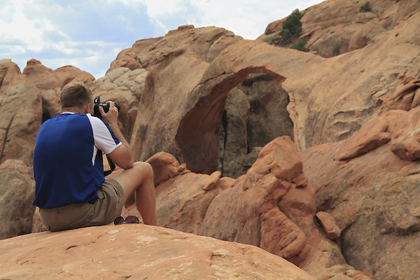 Photographer and Double O Arch in Arches National Park, Utah, Utah. .  John offers private photo tours in Arches National Park and throughout Utah and Colorado. Year-round.