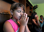 A girl prays in the children's class of the United Methodist Church in the largely Roma neighborhood of Gorno Ezerovo, part of the Bulgarian city of Burgas. Residents here don't self-identify much as Roma, because of the negative connotations associated with the word, so many refer to themselves as a Turkish-speaking minority.