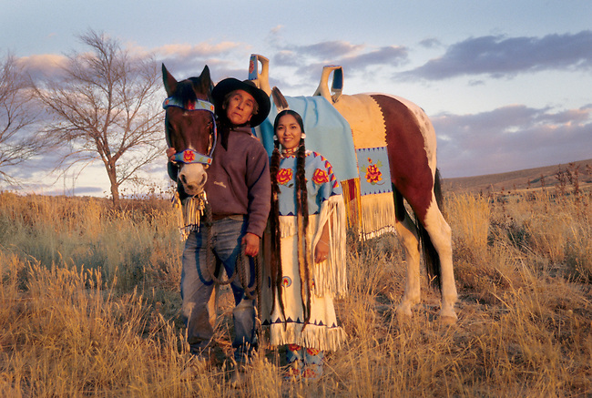 Native American family of Shoshone Bannock cowboy father with traditionally dressed daughter and horse covered in beaded regalia.