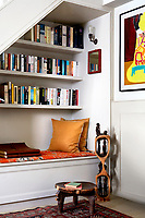 In the book-lined alcove beneath the stairs, the bench doubles as a storage space