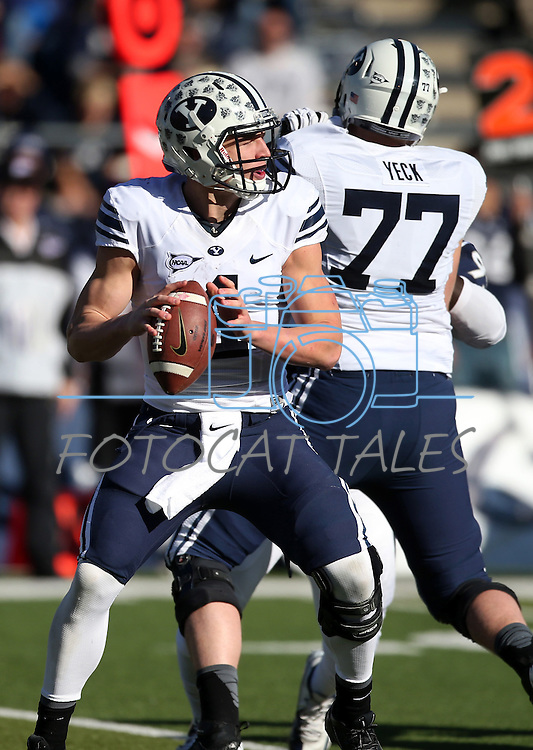 BYU quarterback Taysom Hill (4) looks to pass against Nevada in an NCAA college football game in Reno, Nev., on Saturday, Nov. 30, 2013. BYU defender Michael Yeck (77) is at rear. (AP Photo/Cathleen Allison)