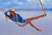 A woman wearing a straw hat laughs while swinging in a hammock at the beach.