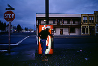 Cowboy stops for a break at a coke machine on Main Street of town in early morning.