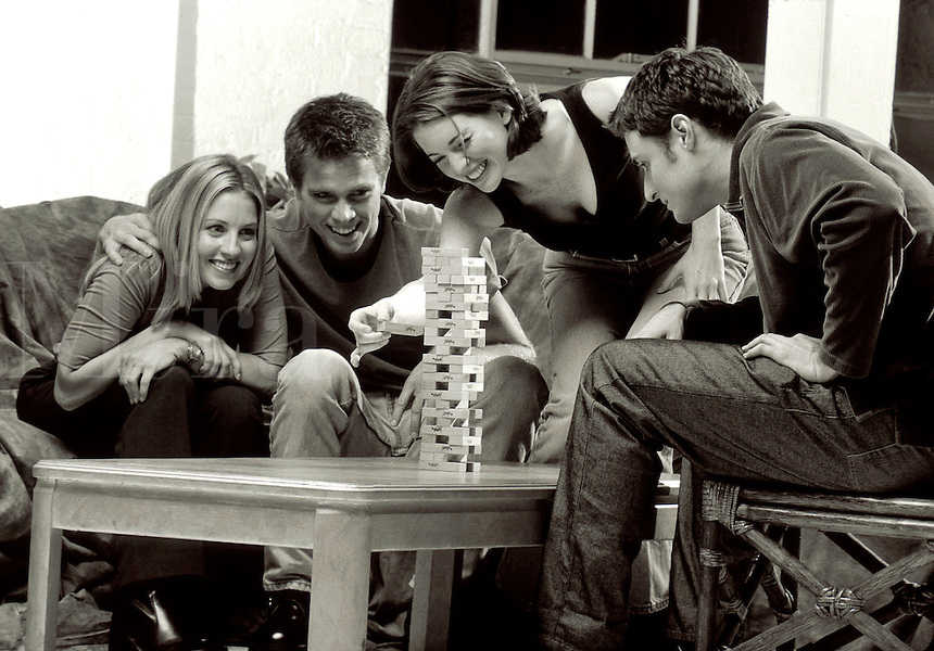 Smiling young couples playing a game of Jenga.