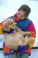 Girl holding her golden retriever puppy outdoors.