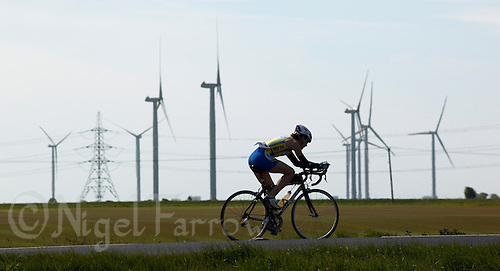 16 MAY 2010 - LYDD, GBR - A competitor passes the Little Cheyne Wind Farm during The Marshman Triathlons .(PHOTO (C) NIGEL FARROW)