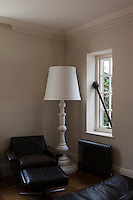 A brown eather armchair and footsool with an oversize floor lamp behind in the corner of the sitting room in Whitehouse, a guest house in Chillington, Devon