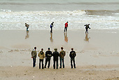 Young men throw stones into the sea at the Yorkshire seaside resort of Bridlington on Easter Bank Holiday.