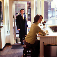 Woman sitting in cafe with man coming through door in background