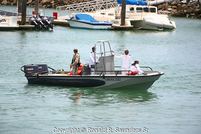 Mexican military representatives in small watercraft. <br />  The occasion is a cause for pride in the Mexican navy. (3)