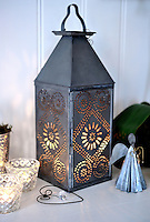 A metal lantern with a punched out decorative pattern and a Christmas angel are displayed on the sideboard in the dining area