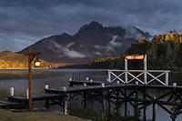 Llao Llao Hotel jetty by lake at dusk next to cloudy mountains in Bariloche, Argentina
