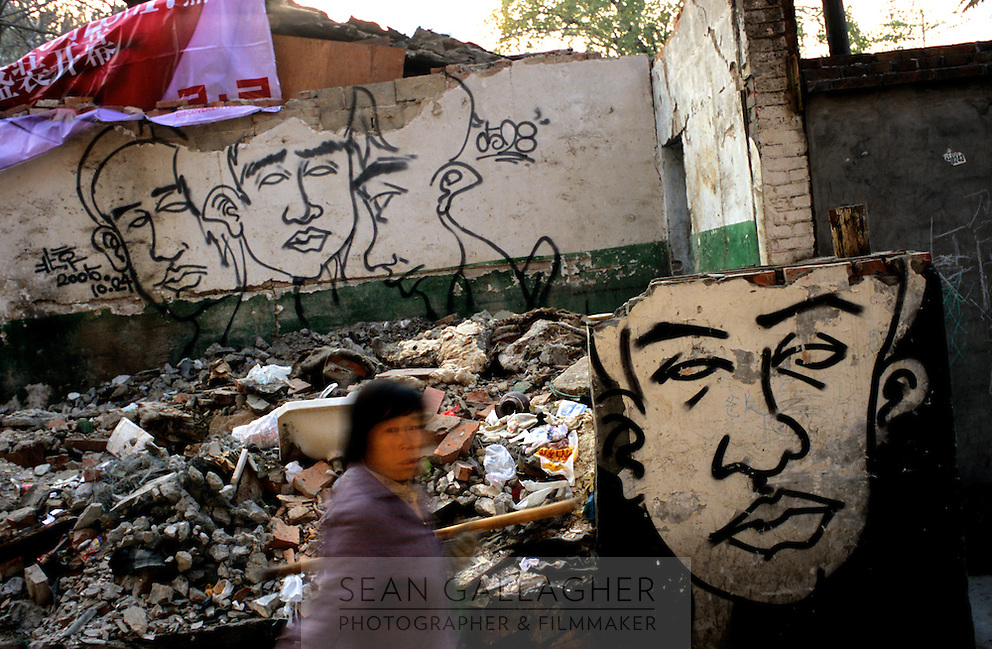 CHINA. Beijing. A woman walks past a graffitied wall in a destroyed hutong (tradtional home) making way for new developments aimed at modernising the city for the 2008 Summer Olympics. 2005