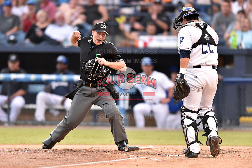Asheville Tourists catcher Chris Rabago (22) shows home plate umpire Sam Burch the ball as calls the runner out during a game against the Hagerstown Suns at McCormick Field on September 4, 2016 in Asheville, North Carolina. The Suns defeated the Tourists 10-5. (Tony Farlow/Four Seam Images)