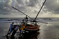 Brazilian fishermen (jangadeiros) push their boat towards the ocean at the sunrise on the beach of Uruaú, Ceará state, northeastern Brazil, 16 March 2004. Jangadeiros, working on a unique wooden raft boat called jangada, keep the tradition of artisan fishing for more than four hundred years. However, being a fisherman on jangada is highly dangerous job. Jangadeiros spend up to several days on high-sea, sailing tens of kilometres far from the coast, with no navigation on board. In the last two decades jangadeiros have been facing up the pressure from motorized vessels which use modern, effective (and environmentally destructive) fishing methods. Every time jangadeiros come back from the sea with less fish.