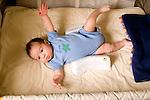 2 month old baby boy on back in crib full length newborn reflex startle moro reflex Hispanic Puerto Rican