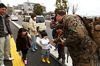 U.S. Navy Lt. Boyce Gire, a medical planner with the humanitarian assistance survey team, III Marine Expeditionary Force (Fwd) hands candy to Japanese children during a survey of the Tagajo City Cultural Center March 21. The Cultural Center is being utilized as an internally displaced persons camp for residents affected by the earthquake and subsequent tsunami that struck mainland Japan March 11, causing widespread damage. As part of Operation Tomodachi, the HAST stands ready to support our Japanese partners and to provide assistance when called upon.