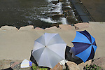 Couple under umbrellas at Boulder Creek, Boulder, Colorado. .  John offers private photo tours in Denver, Boulder and throughout Colorado. Year-round.