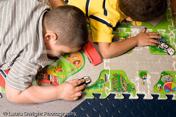 Education Preschool 4-5 year olds.Educaton preschool 4-5 year olds closeup of two boys on rug with roads printed on it playing with small cars or vehicles horizontal
