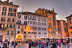 As the sun begins to set, lights come on, the bars around the plaza open, and tourists mix with locals around the central fountain (the Fontana del Pantheo) in the Piazza della Rotonda, in front of the Pantheon in Rome, Italy.