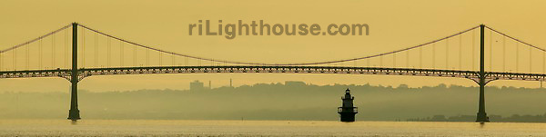 he Mount Hope Bridge and Lighthouse at Hog Island at a beautiful evening sunset off Bristol, RI in Narragansett Bay.