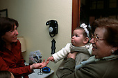 Seville, Spain. Three generations: grandmother, aunt and baby in a flat with a telephone and a thermometer on the wall.