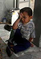 """Gaza.June.22.2008.Ahmad Jilo  a four-year-old  thinking about his life  among graves, he was born and grew up in the cemetery , """"he don't go out from this place and he don't fear from the tombs because we live and play here.""""The family was drove out from their original village in the 1948 when Jews  forced thousands of Palestinians to migrate, establishing the State of Israe.June.22.2008l.""""photo by Fady Adwan/propaimages"""""""