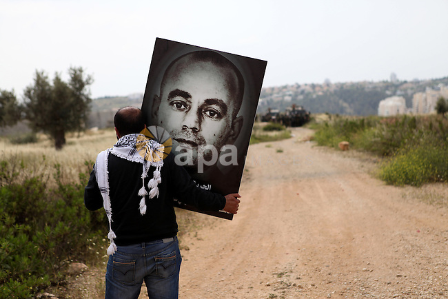 A Palestinian man holds a banner in front of Israeli security forces during a demonstration marking Palestinian Prisoners' Day, in the West Bank village of Bilin, near Ramallah on April 17, 2015. Palestinian human rights groups say 6,000 Palestinian prisoners remain in Israeli prisons and detention camps. Photo by Shadi Hatem